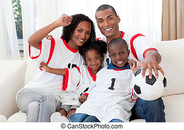 Afro-American family celebrating a football goal - Happy...