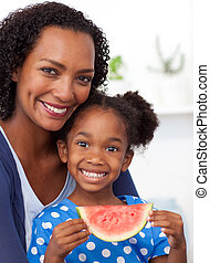 Mother and daugther eating a slice water melon