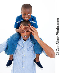 Close-up of a father giving son piggyback ride with closed...