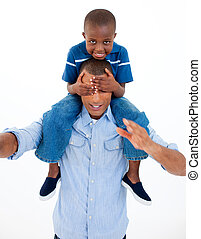 Dad giving son piggyback ride with closed eyes against white...