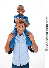 Happy father giving son piggyback ride against white...