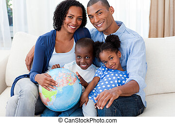 Afro-american family holding a terrestrial globe on the sofa