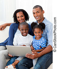 Happy family using a laptop in the living-room