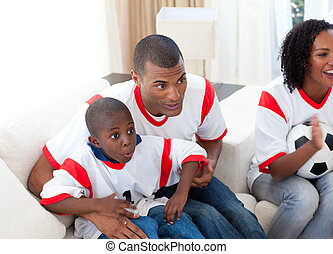 Happy family watching a football match