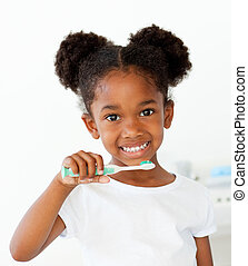 Portrait of an Afro-american girl brushing her teeth in the...
