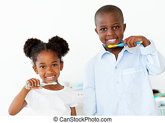 Smiling brother and sister brushing their teeth in the...