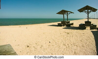 Beach umbrellas and wooden tables and on the beach. Shadow moves.