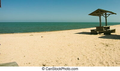 Beach umbrellas and wooden tables and on the beach. Shadow...
