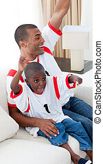 Happy father and his son celebrating a goal on sofa