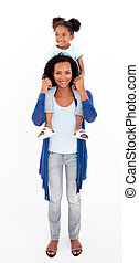 Mother giving happy daughter piggyback ride - Afro-american...