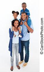 Family giving children piggyback ride against white...