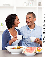 Smiling lovers having healthy breakfast at home