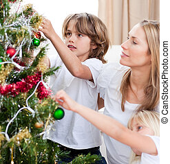 Children hanging Christmas decorations with their mother