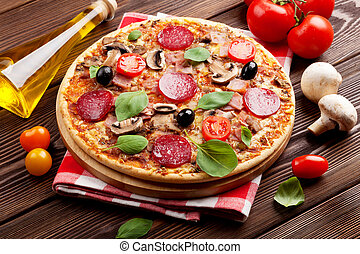 Italian pizza with pepperoni, tomatoes, olives and basil on...
