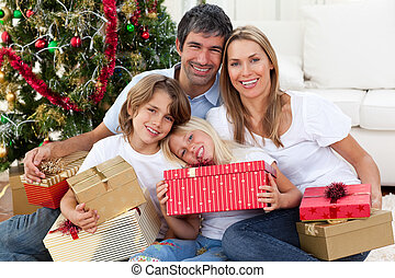 Happy family holding Christmas gifts and sitting on the...