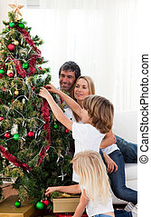 Smiling family hanging decorations on a Christmas tree