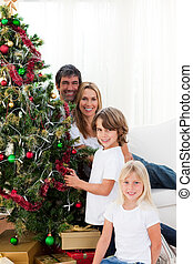 Happy family decorating a Christmas tree with baubles