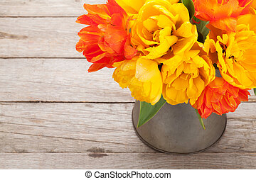 Colorful tulips bouquet in watering can on wooden table Top...