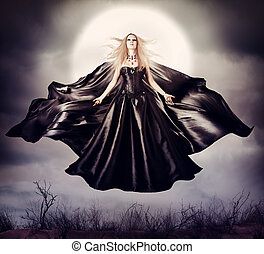 Beautiful woman - flying halloween witch in midnight outdoor...