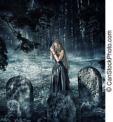 woman in black dress praying on cemetery