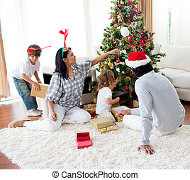 Family decorating a Christmas tree at home