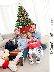 Portrait of a smiling family holding Christmas presents