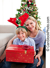 Portrait of a mother and her son holding Christmas gift