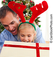 Father and his daughter opening Christmas gifts at home