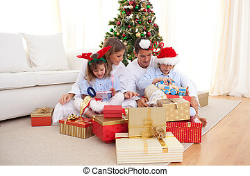 Young family unpacking Christmas presents - Young family...