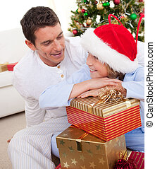 Smiling father and his son unpacking Christmas gifts