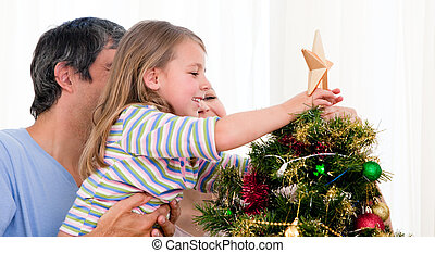 Smiling family decorating a Christmas tree in the living-room