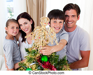 Happy family decorating a Christmas tree in the living-room