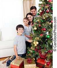 Happy family decorating a Christmas tree with boubles and presents in the living-room