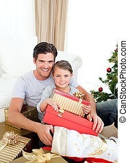 Happy little girl with her father holding a Christmas gift