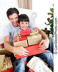 Happy father and son holding Christmas presents