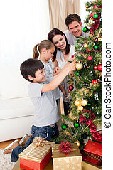 Smiling family decorating a Christmas tree at home - Smiling...