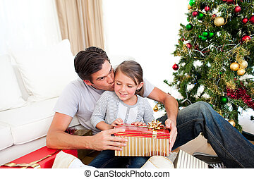 Happy little girl with her father holding a Christmas gift at home