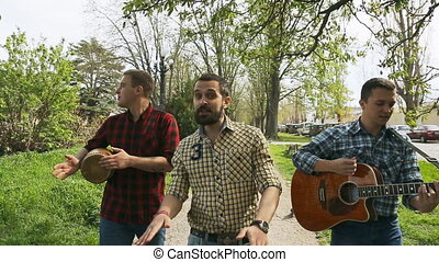 Talented guys in plaid shirt walking down the street and...