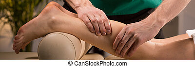 Squeezing the calf - Close-up of masseur squeezing the calf...