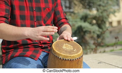 Close-up of a guy in a plaid shirt beating on a drum