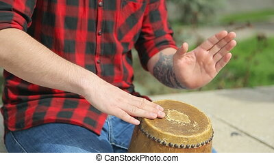 Close-up of a guy in a plaid shirt beating on a drum -...