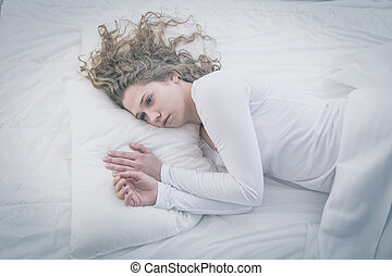 Patient of mental hospital lying in bed