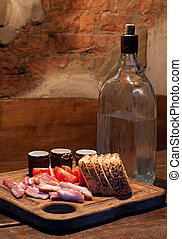 Russian Vodka and bacon, tomato and bread on wooden table
