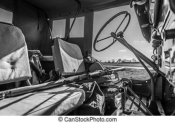 Black and white interior of WW2 Jeep with rifle across seat....