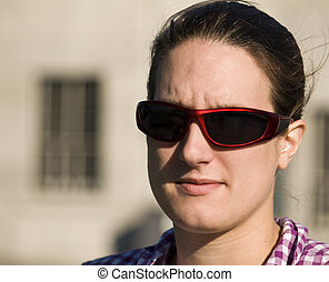 a portrait of a beautiful young woman wearing red sunglasses...