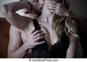 Man caresses neck and breast of woman in bed