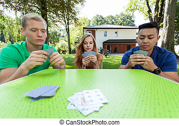 Card game - Young student playing cards and spending nice...