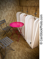 Urinal - Table and garden chairs in a urinal