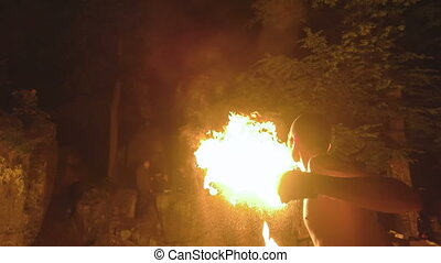 Fire show - Caucasian man spitting fire as a part of fire...