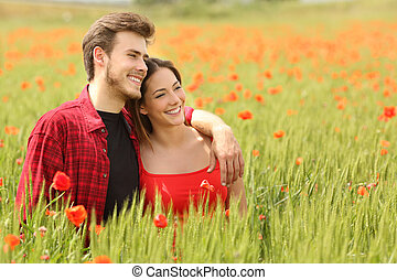 Couple hugging and walking in a green field with red flowers...